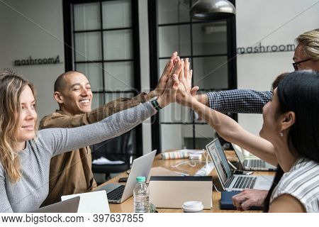 Team of business people high fiving during the meeting