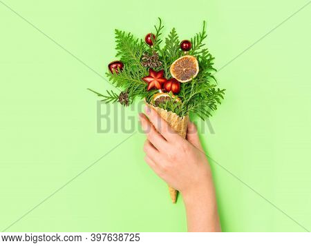 A Female Hand Holds A Favela Horn With Thuja Sprigs And Christmas Toys On A Green Background. New Ye