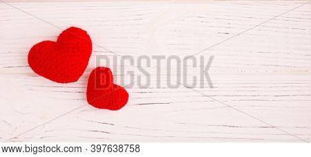 Two Knitted Hearts On White Wooden Background. Valentines Day, Love, Minimalism, Greeting Card Conce