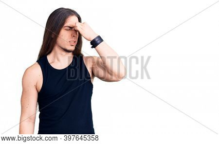 Young adult man with long hair wearing goth style with black clothes tired rubbing nose and eyes feeling fatigue and headache. stress and frustration concept.