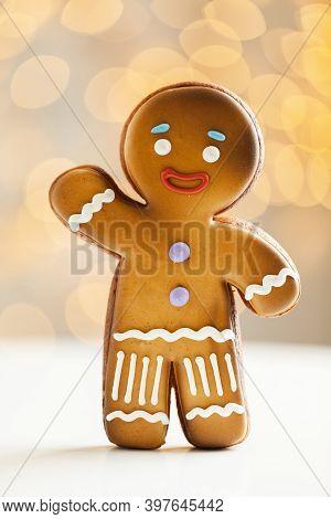 Gingerbread Man Cookie On The Blurred Christmas Lights Background. Warm Bokeh Lights. Macro Shot. Ne
