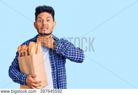 Handsome latin american young man holding paper bag with bread cutting throat with hand as knife, threaten aggression with furious violence