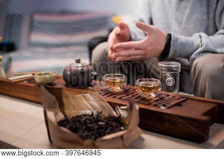 Close-up Of The Chinese Tea Ceremony Ritual. Hands Pour Hot Water Into Special Vessels On A Bamboo B