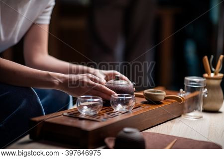 Traditional Chinese Yixing Clay Teapot In Womens Hands Close-up. A Girl Performs The Sacrament Of An
