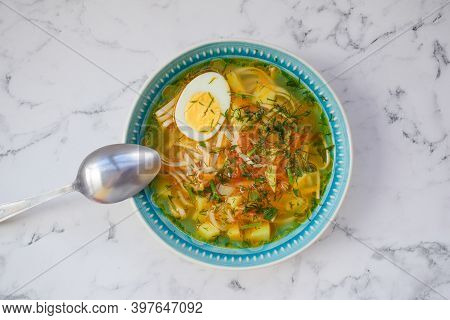 Udon Noodle Soup In A Blue Plate And Metal Spoon With Egg, Potatoes And Fresh Herbs