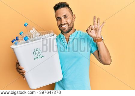 Handsome man with beard holding recycling wastebasket with plastic bottles doing ok sign with fingers, smiling friendly gesturing excellent symbol