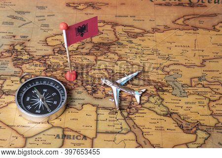 Flag Of Albania, Compass And Plane On The World Map.