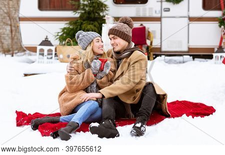 Romantic Young Lovers Enjoying Picnic During Winter Day At Camping, Sitting On Red Plaid On Snow, Dr