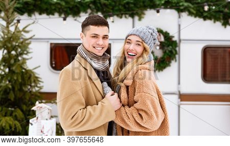 Outdoor Portrait Of Romantic Couple Spending Date On Winter Day At Campsite, Cuddling And Posing Nea