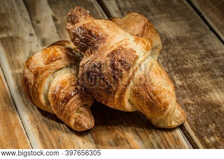 Two Freshly Baked Croissants On Wooden Table