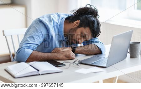 Sleeping At Work. Overworked Freelancer Guy Napping At Workplace At Home Office, Tired After Working