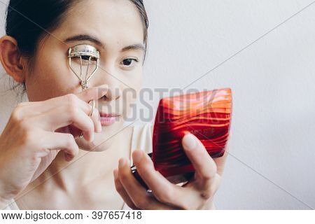 Portrait Of Young Asian Woman Looking At The Mirror Using Eyelash Curler. Eyelash Curler Is A Hand-o