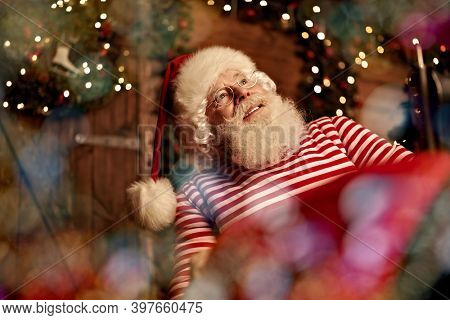 Santa Claus workshop. Santa Claus is preparing for Christmas at his wooden home - he sews gifts on a sewing machine. Christmas decoration.