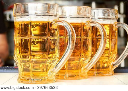 Three Glasses Of Fresh Foamy Beer On The Bar Counter