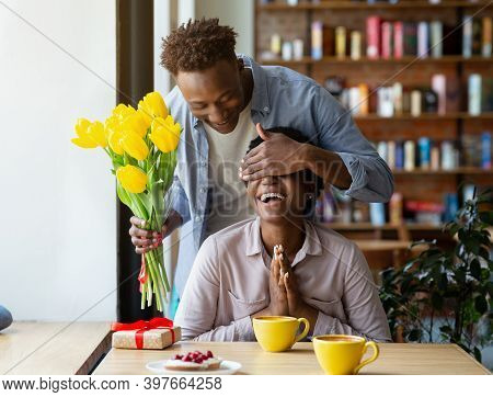 Loving Black Guy Surprising His Girlfriend With Beautiful Yellow Tulips At Coffee Shop. Affectionate