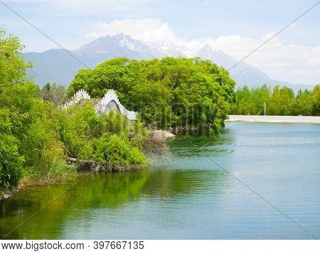 Qingxi Reservoir And Beautiful Bridge With Jade Dragon Snow Mountain In The Background. Lijiang, Yun
