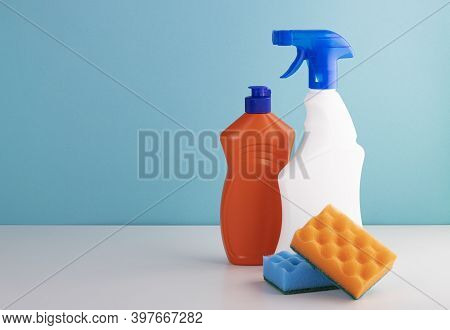 Cleaning Products On A Blue Background With Space For Text. The Concept Of Cleaning And Cleanliness