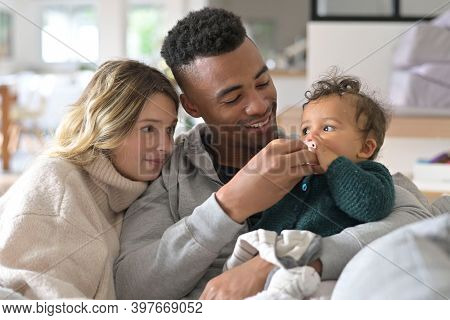Young mixed-raced family at home cuddling baby girl