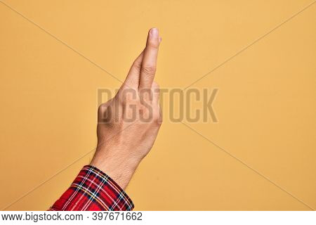 Hand of caucasian young man showing fingers over isolated yellow background gesturing fingers crossed, superstition and lucky gesture, lucky and hope expression