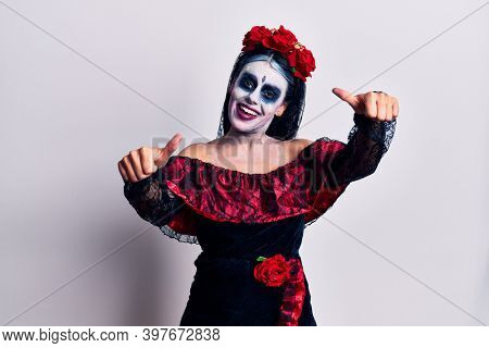 Young woman wearing mexican day of the dead makeup approving doing positive gesture with hand, thumbs up smiling and happy for success. winner gesture.