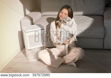 Woman With Her Cat Breathing Fresh Air At Home. Air Purifier Or Humidifier In A Living Room. Dehumid