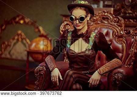 Beautiful steampunk woman sits in an armchair in a room with vintage victorian interior. Science fiction, adventures.