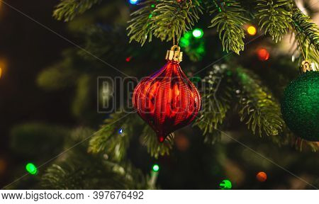 Beautiful Christmas Tree With Red Toy On Branches Close Up. Concept Of A New Year Atmosphere And Fes