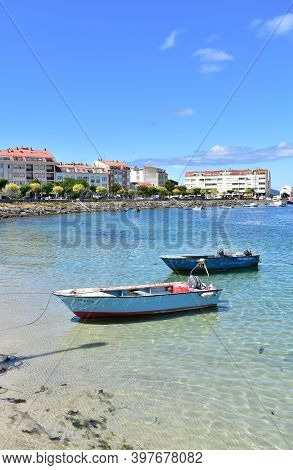 Portosin, Spain. June 30, 2020. Harbor And Coastal Village With Rowboats And Galician Fishing Vessel