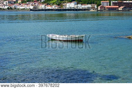 White Wooden Rowboat Floating On The Sea Moored At Famous Rias Baixas In Galicia Region. Muros, A Co