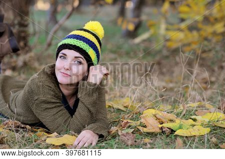 Young woman portrait, resting outdoor in park, dressed in knitted hat with pompom, looking at camera