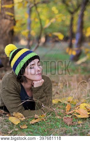 Young woman portrait, resting outdoor in autumn park, dressed in knitted hat with pompom