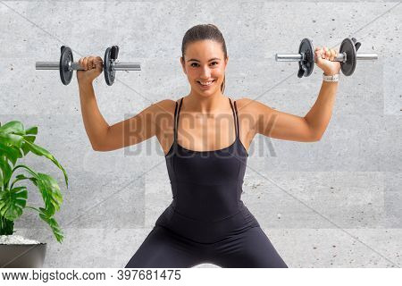 Close Up Portrait Of Cute Young Woman Doing Shoulder Exercise With Dumbbells At Home.