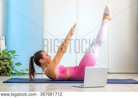 Young Woman Doing Boat Yoga Pose In Living Room. Girl Attending Online Yoga Class At Home In Front O