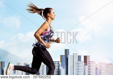 Close Up Action Portrait Of Young Woman Jogging With City. Girl In Sportswear Running With Skyscrape
