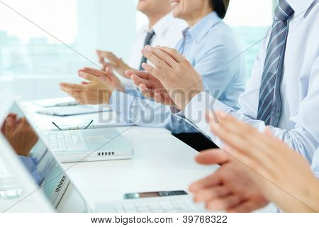 Business people sitting in a row applauding to their successful colleague
