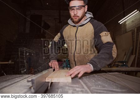 A Worker Processes A Board On A Woodworking Circular Machine