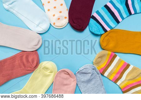 Many Socks Are Piled In A Circle In Blue Background. View From Above.