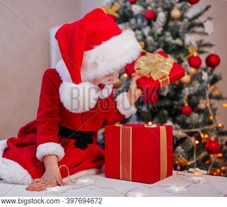 Merry Christmas And Happy Holidays. Funny Cute Girl In Surprise And Delight Opens The Gift. A Child