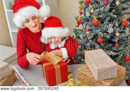 A Mother With Her Daughter In Santa Hats Packs A Gift And Ties A Bow On A Red Gift Box Together Befo