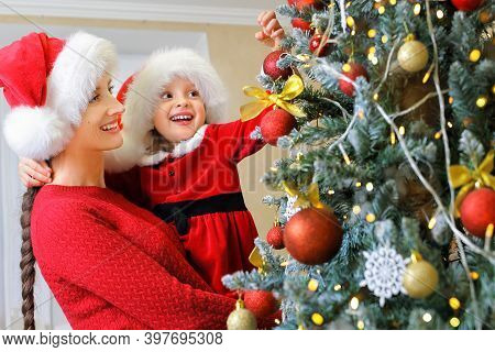 A Mother And Her Kid In A Santa Hats Decorates The Christmas Tree With Baubles On Christmas Eve, And
