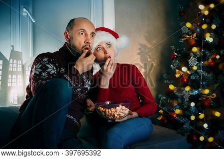 A Husband And His Wife Enjoy Popcorn While Watching Tv On Christmas Eve And Watch Movies With Their