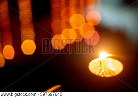 Shot Of Diya Oil Lamp Emitting Smoke With Out Of Focus Bokeh String Lights In The Background On The
