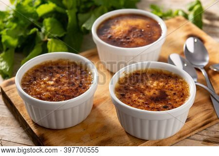 Homemade Creme Brulee In Bowl On Wooden Table