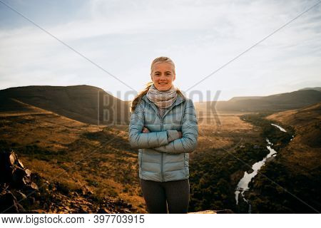 Caucasian Female Standing Cross-armed On Top Luscious Mountain