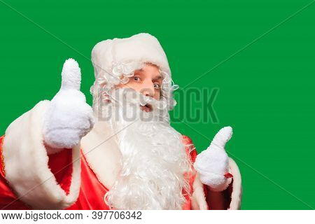 Young Men Dressed In Santa Claus Costume With Thumb Up Sign Isolated On Green Background.