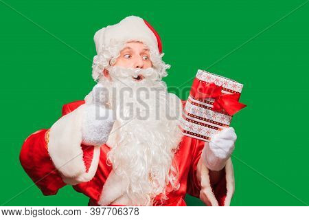 Santa Claus Holding Nicely Wrapped Christmas Present Isolated On Green Colored Background.