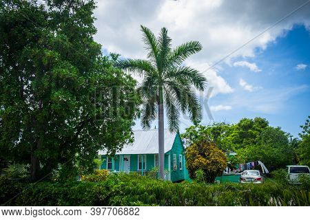 Grand Cayman, Cayman Islands, July 2020, View Of A Green Wooden Traditional House With A Tin Roof Su