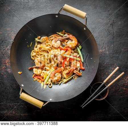 Chinese Wok. Udon Noodles In A Wok Pan With Chopsticks And Soy Sauce. On Dark Rustic Background