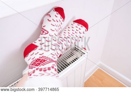 Feet In Christmas Socks Getting Warm On A Central Heat Radiator, Winter Home Relax And Rest.