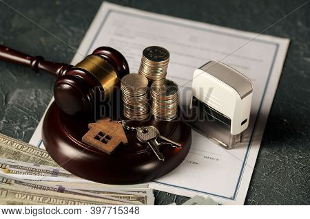 A Row Of Coins On A Small House Model And A Law Auction Hammer